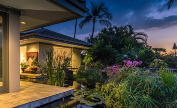 Photo of a beautiful luxury Big Island home, outside lanai area, garden and lily pond against a sunset night sky